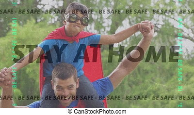 Animation of words Be Safe Stay At Home flashing Over caucasian man playing outside with his son