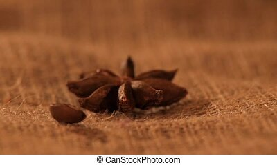 Anise on sacking, and falling coffee beans, close up