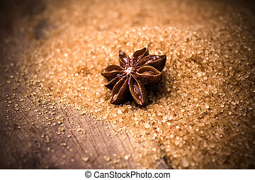 Anise star on brown cane sugar on wooden background, christmas s