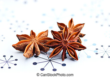 Three anise stars on a holiday background.
