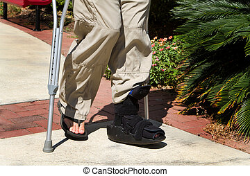 Ankle Brace Crutches - Man uses crutches along with a foot...