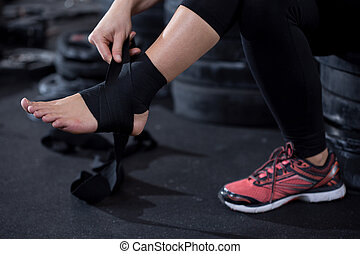 Ankle injury - Girl with ankle injury preparing to workout