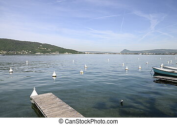 Annecy lake and city and wooden pontoon with boats