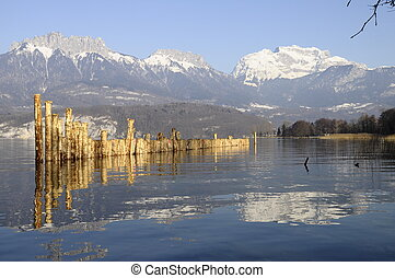 Annecy lake and mountains of Tournette and Forclaz with wooden poles in foreground