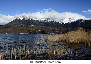 Annecy lake and snow on mountains, winter landscape in Savoy, France