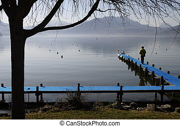 Annecy lake and woman with dog on blue pontoon