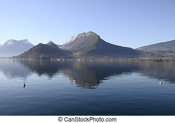 Annecy lake from Talloires and view upon mountains and reflections in blue water lake