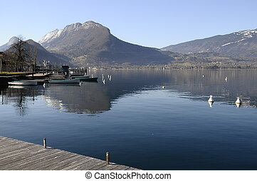Annecy lake from Talloires harbour and wooden pontoon on morning