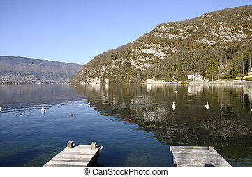 Annecy lake from Talloires harbour, mountain of roc de chere,  and wooden pontoons on morning
