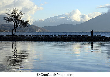 Annecy lake landscape, snow on mountains, Savoy, France