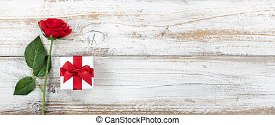 Anniversary background with a single red rose and gift box on white weathered wood