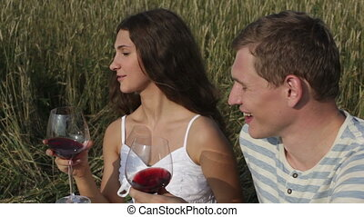Couple celebrating their anniversary in the countryside drinking wine