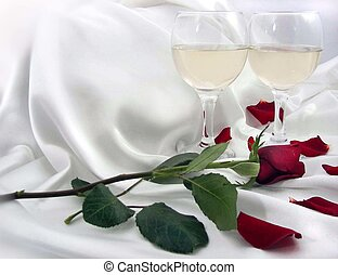 Long stem rose with wine glasses on satin.