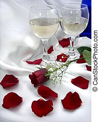 Anniversary Night - Wine in glasses with rose petals on...