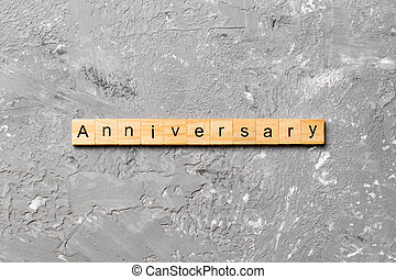 anniversary word written on wood block. anniversary text on cement table for your desing, concept