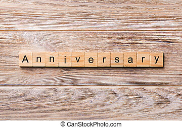anniversary word written on wood block. anniversary text on wooden table for your desing, concept