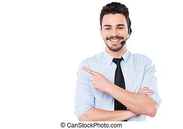 annonsering, din, product., stilig, ung, manlig, operatör, pekande, bort, och, le, medan, stående, mot, vit fond