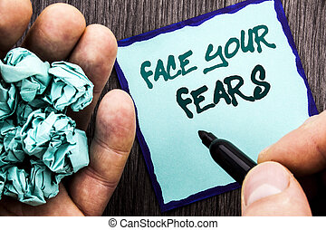Announcement text showing Face Your Fears. Business concept for Challenge Fear Fourage Confidence Brave Bravery written on Notebook Book Man Writing Holding Pen wooden background.