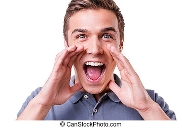 Announcing good news. Happy young man holding hands near mouth and shouting while standing isolated on white background