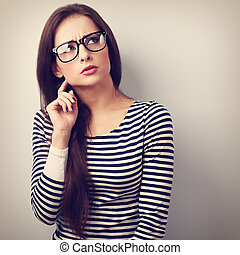 Annoyed angry young woman in eyeglasses thinking and looking up. Vintage closeup portrait