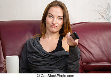 Annoyed beautiful young woman using tv remote control on...