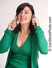Annoyed brunette talking with two phones - Hysterical...
