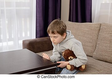 Annoyed child sitting on the sofa and watching tv