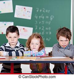Annoyed children - Three annoyed children sitting in the...