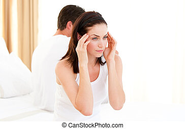 Annoyed couple having an argument sitting on their bed