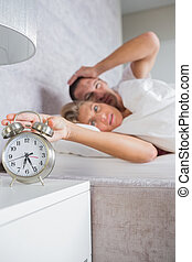 Annoyed couple looking at alarm clock in the morning with...