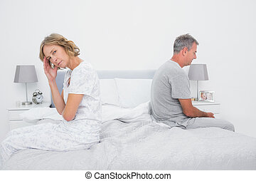 Annoyed couple sitting on different sides of bed