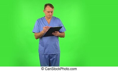 Annoyed doctor fills papers at black folder with pensil. Green screen