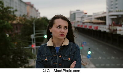 annoyed girl standing on bridge expresses her dissatisfaction, frustration negative emotions and looks at the camera.