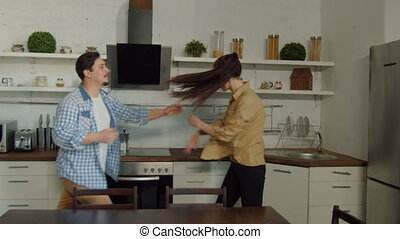 Young couple quarreling in domestic kitchen, blinded by jealousy husband shouting, pushing wife, blaming in adultery. Angry woman slapping man during fighting irritated by unfounded accusations.