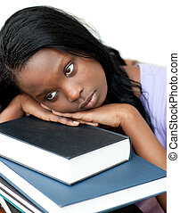 Annoyed student leaning on a stack of books