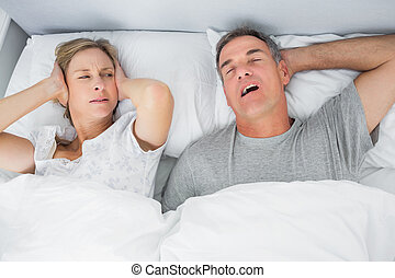 Annoyed wife blocking her ears from noise of husband snoring...