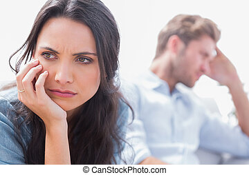 Annoyed woman holding her head next to her husband