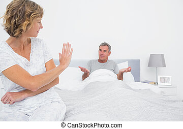 Annoyed woman looking at husband gesturing during a fight in...