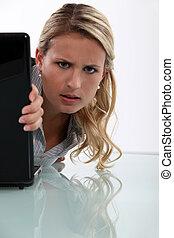 Annoyed woman peeking round her laptop