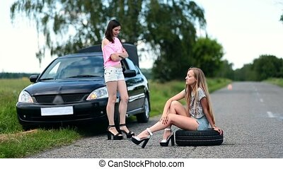 Annoyed woman sitting on spare wheel on the road -...