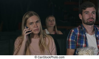 Annoying woman on the phone during movie at the cinema