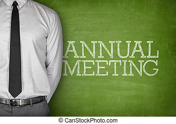 Annual meeting text on blackboard with businessman on side