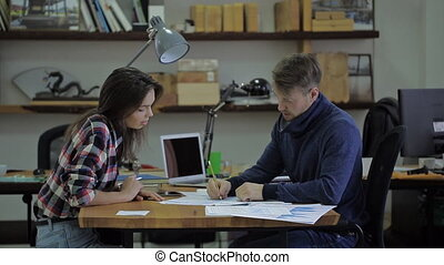 Beautiful hispanic woman in the office with his hipster male expert financial adviser during the meeting. Nearby is a tablet, a laptop and a lamp. She wore a loose modern, feminine shirt. discuss the solution of the active financial flows. Female sit at the large wooden table on the table a few ...
