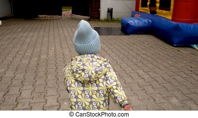 Anonymous child walking towards bouncy castle - Back view of...