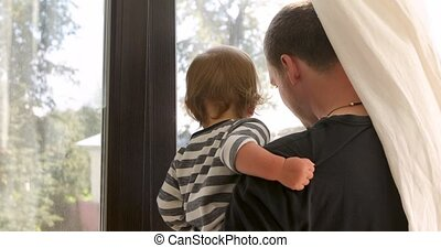 Anonymous father and baby looking out window - Back view of...