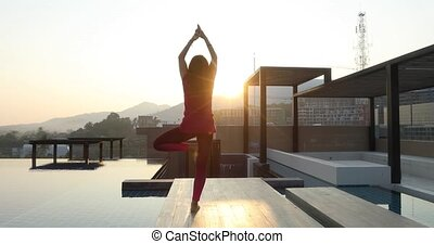 Anonymous female doing yoga on roof