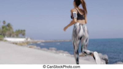 Anonymous girl running on waterfront - Back view of fit girl...