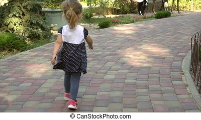 Anonymous girl walking along path in park - Back view of...