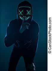 Anonymous man in black hoodie hiding his face behind a neon mask