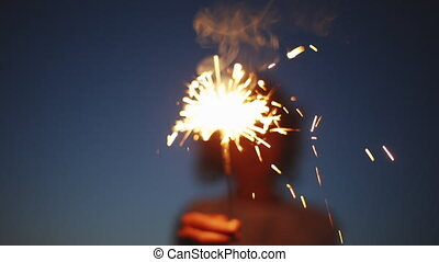Anonymous person with burning firework